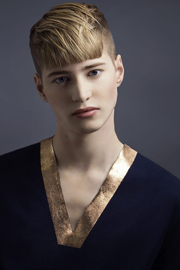 Androgynous male model wearing a futuristic top with a metallic collar.