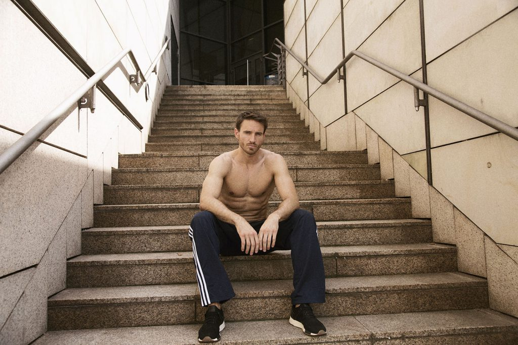 Photo of an athletic man in blue sweatpants sitting on a staircase outside.