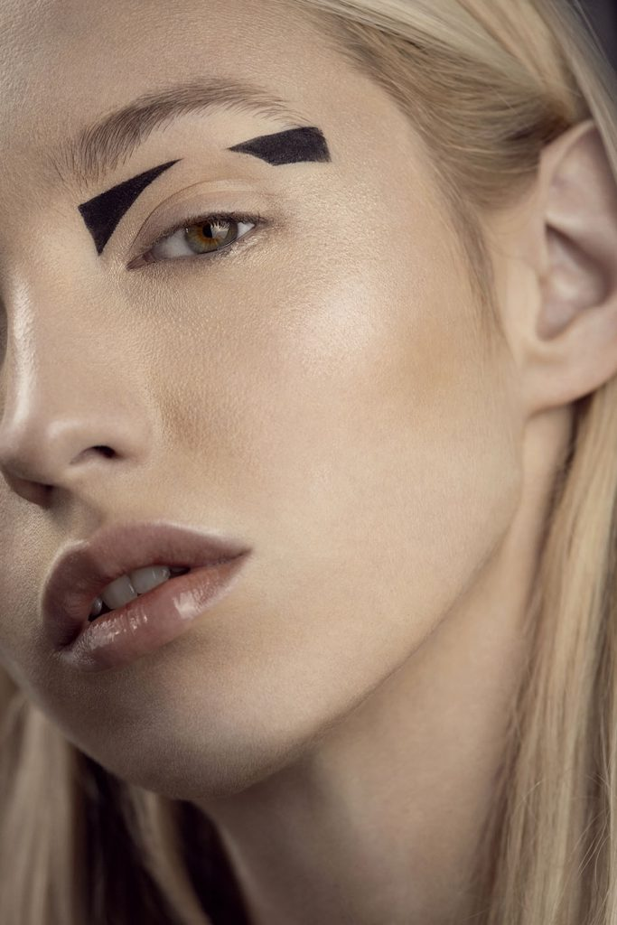 Close-up of model's face with black avant-garde eye make-up.