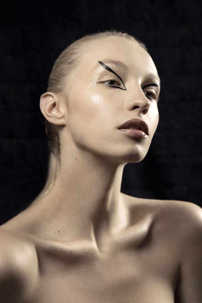Model wearing black avant-garde eye make-up.