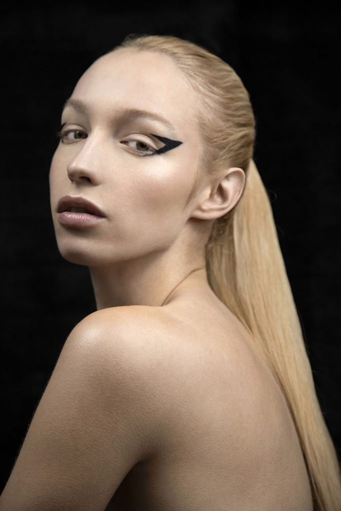 Topless model wearing black avant-garde eye make-up.