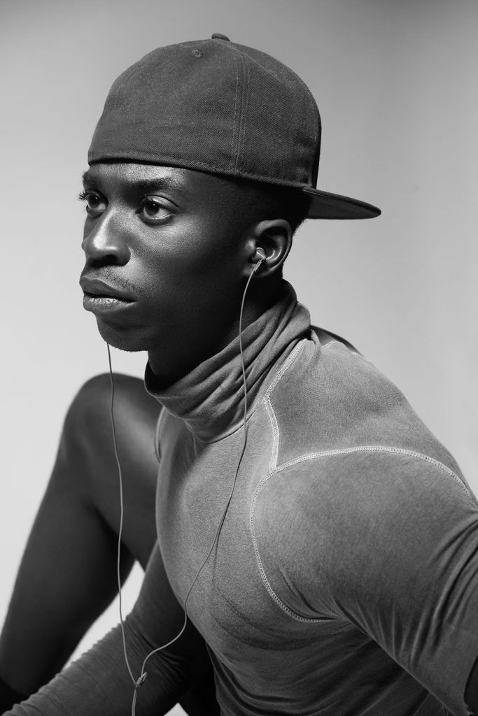 Close-up of a black man wearing a cap, looking off to the side.