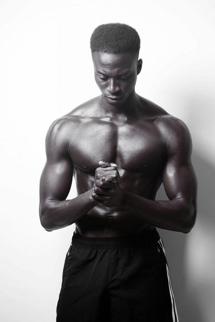 Shirtless black man in a contemplative pose.