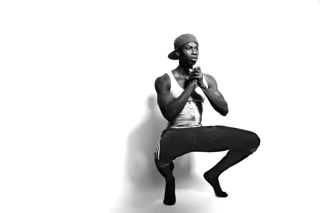 Black athlete in a tank-top and cap  squatting in front of white background.