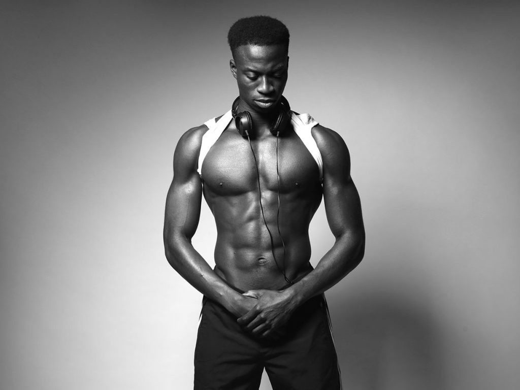 Shirtless black athlete with a pair of headphones around his neck.