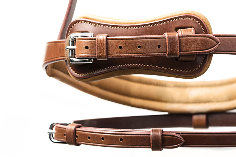 Close-up of brown leather bridle on white background.