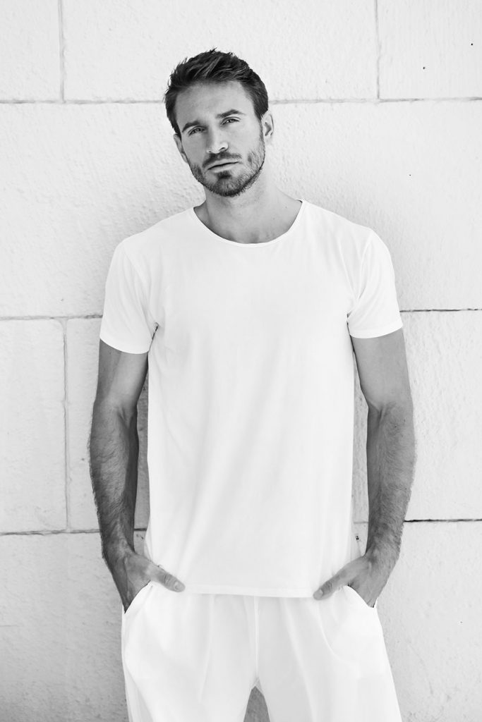 Black-and-white portrait of bearded male model in white T-shirt and white trousers.