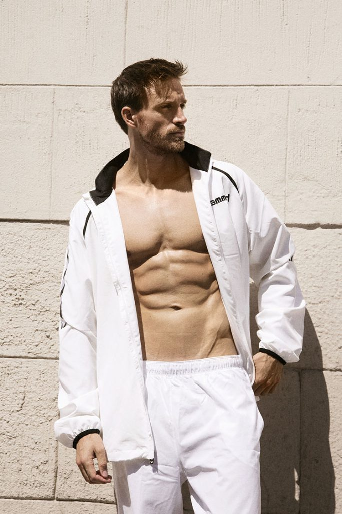 Male model in white tracksuit in front of stone wall.