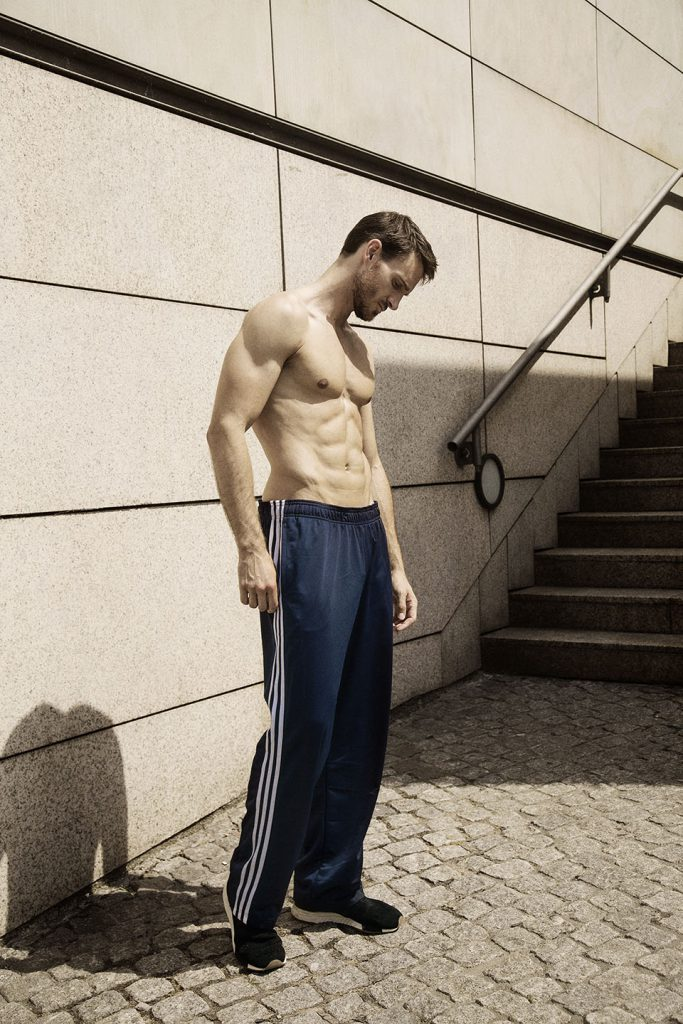 Shirtless male model in blue sweatpants standing in front of stone wall, looking down.