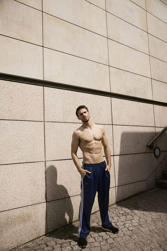 Photo of an athletic man in blue sweatpants standing in front of a facade of large stone blocks.