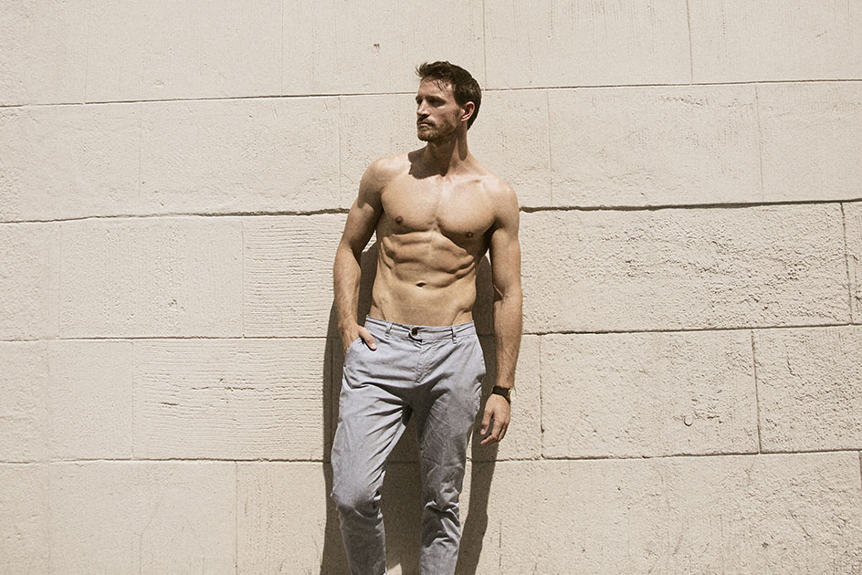 Shirtless male model in grey jeans leaning against stone wall.