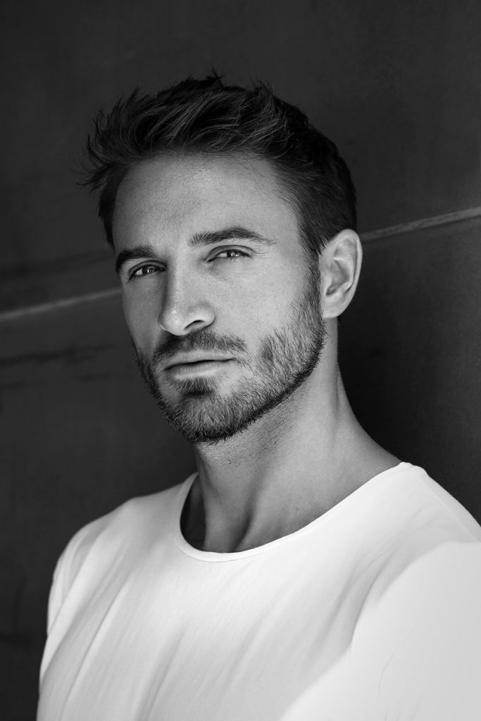 Black-and-white close-up of bearded male model in white T-shirt.