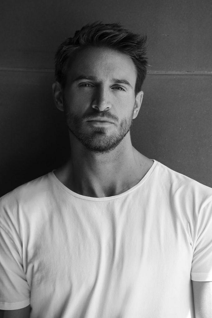 Black-and-white portrait of bearded male model in white T-shirt.