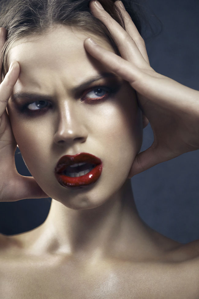 Close-up of model with bold red lipstick looking angrily off to the side in front of a blue background.