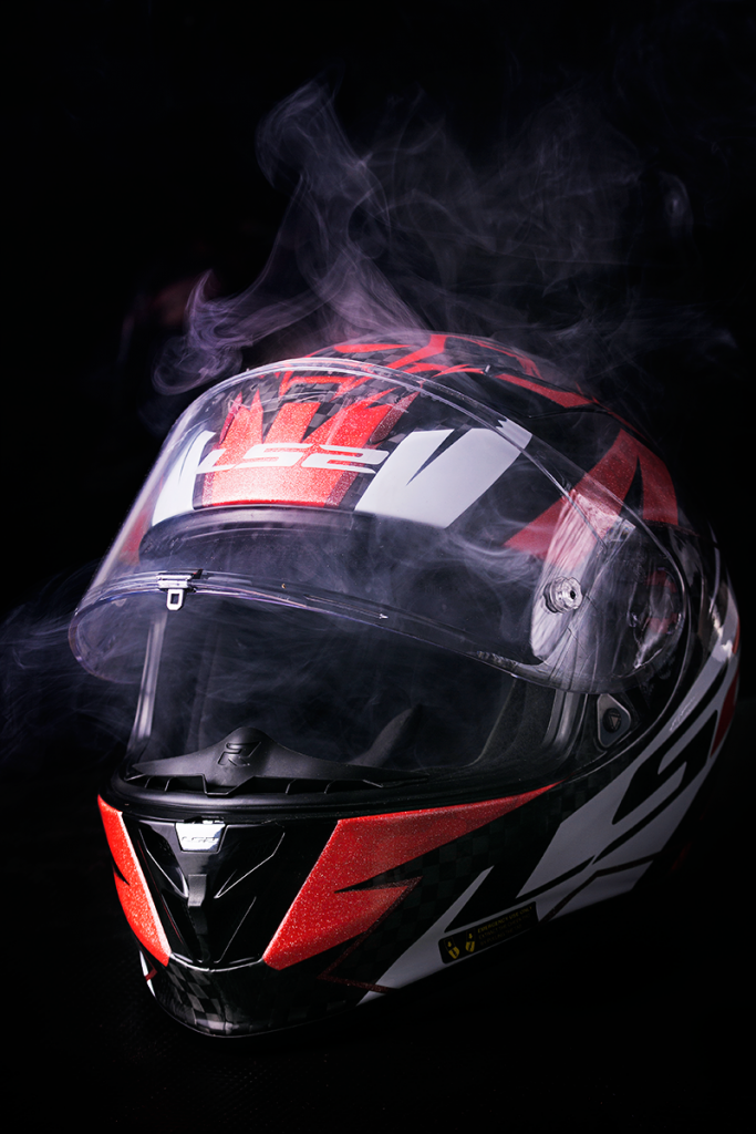 Photo of red and black motorbike helmet with smoke.