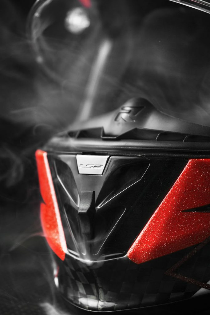 Close-up of red and black motorbike helmet with smoke.