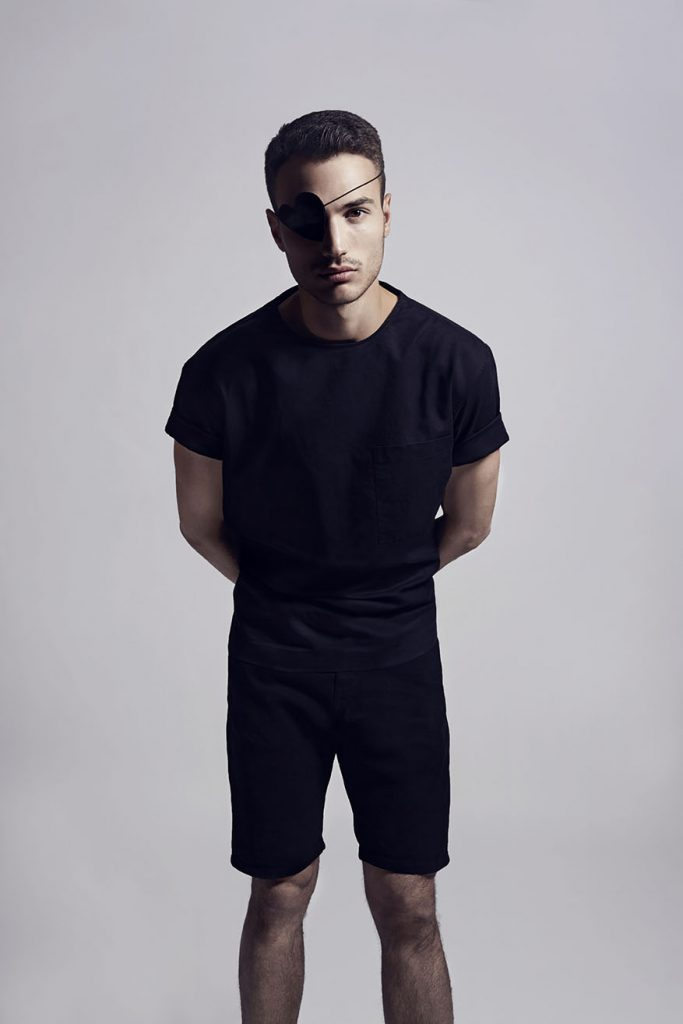 Male model wearing a dark outfit and an eyepatch.