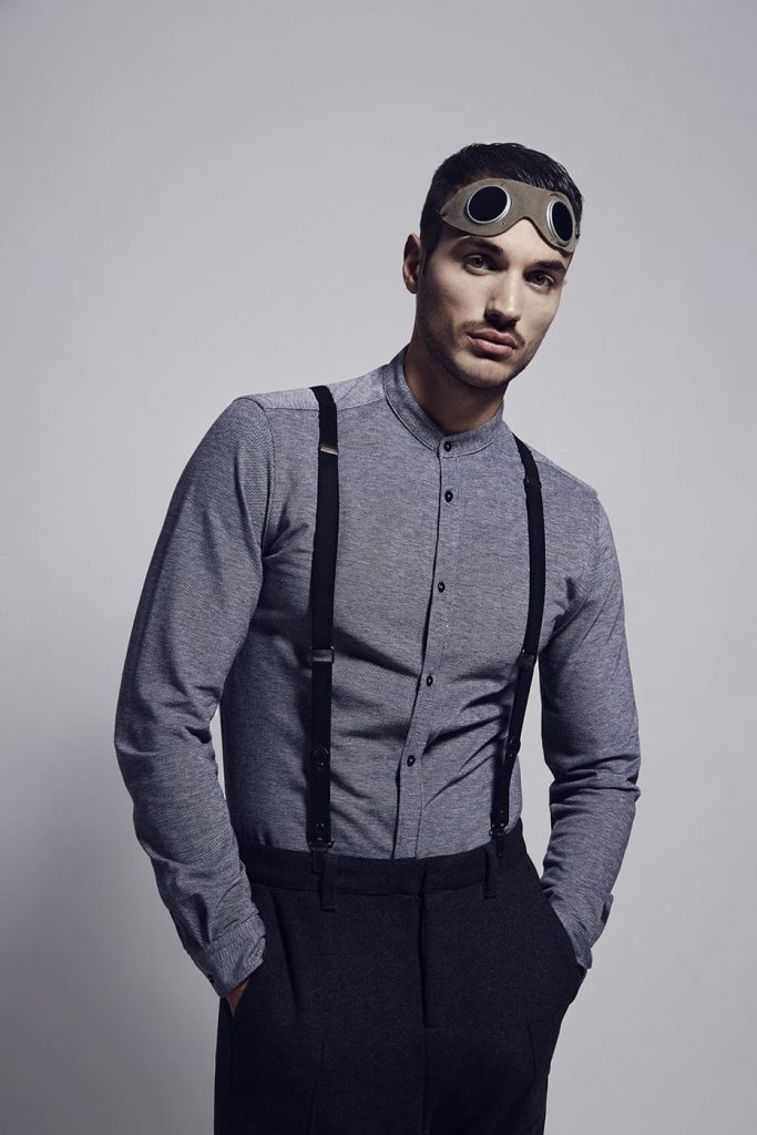 Male model wearing vintage outfit with suspenders and pilot goggles.