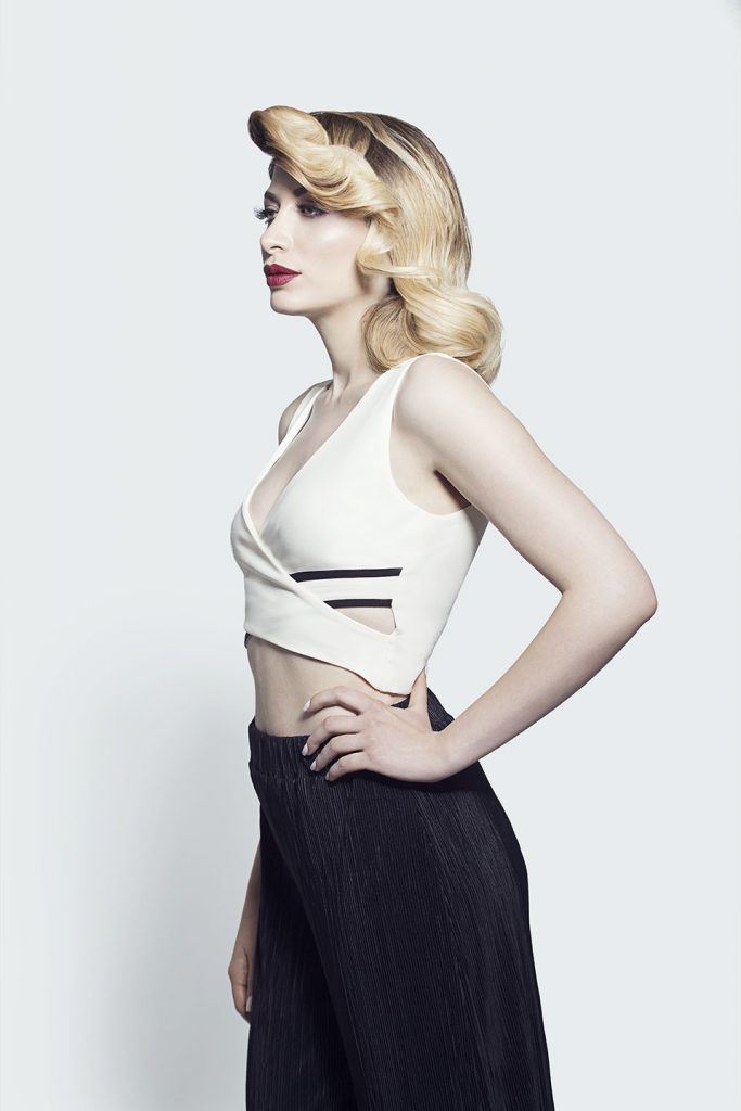 Model with vintage-inspired hairstyle wearing white top and black trousers.