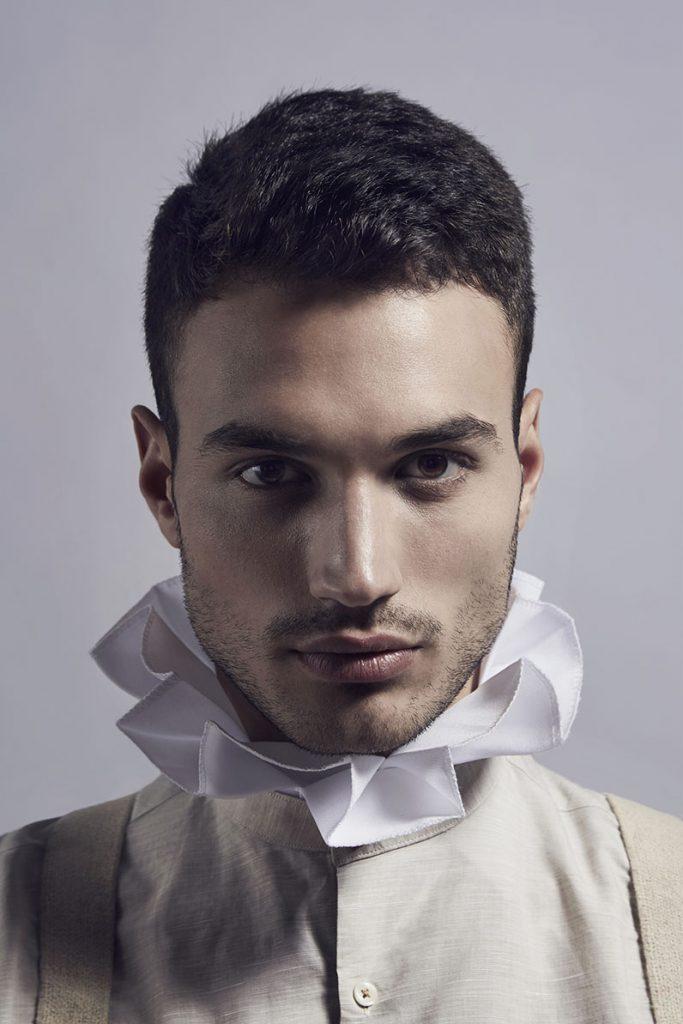 Close-up of male model wearing white ruff.