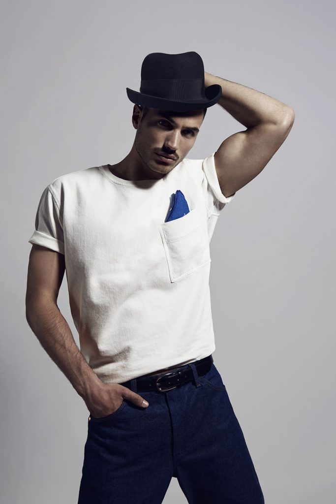 Male model wearing vintage outfit with blue jeans and hat.