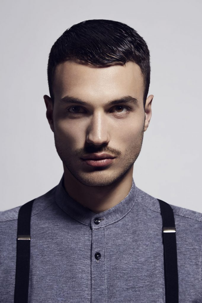 Portrait of male model wearing vintage outfit with suspenders.