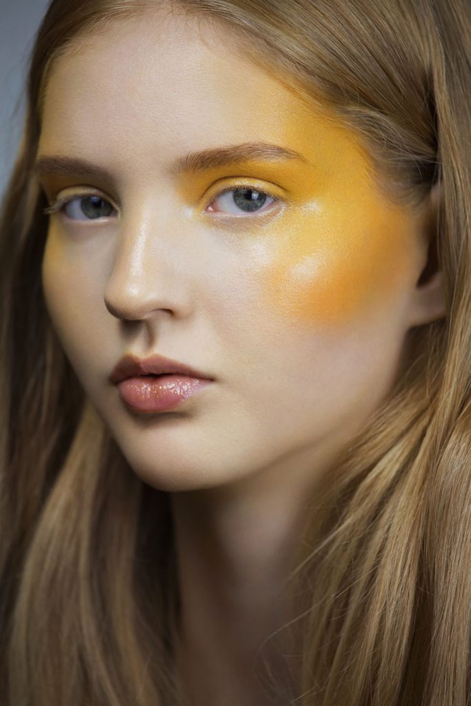 Portrait of model with long blonde hair and avant garde yellow face paint.