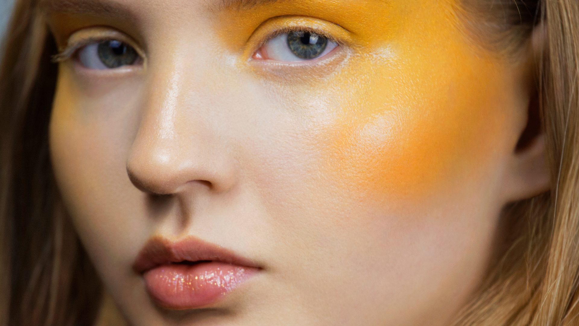 Close-up of woman with yellow face paint.